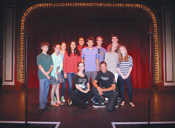 Image of a group of our FastForwad reporters posing on stage with two Beach Blanket Babylon cast members