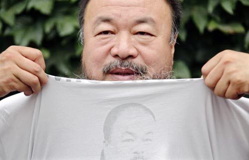 Image of Chinese dissident artist Ai Weiwei pulling up his shirt bearing a portrait of himself as he chats with journalists at the courtyard of his studio before his verdict hearing in Beijing, July 20, 2012.