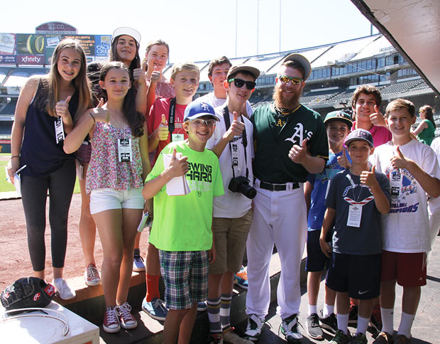 Image of the FastForward Adventure Reporters in the Aokland A's dugout with Sean Doolittle